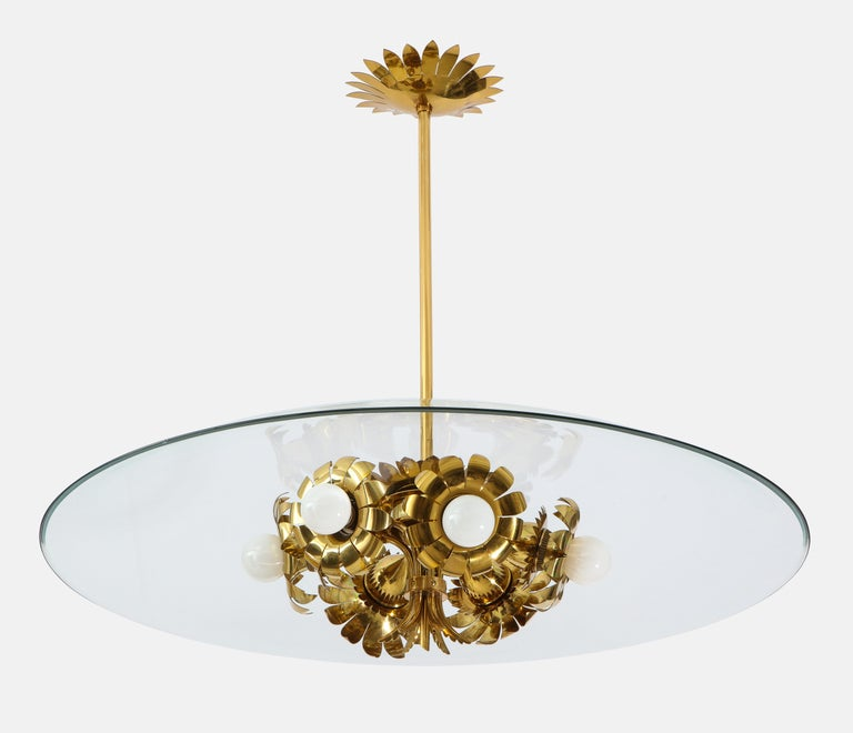 Pietro Chiesa for Fontana Arte rare and important chandelier with lacquered brass structure including six flower shaped socket holders and intricate floral motif decorations, large beveled clear glass disc, and original canopy, Italy, circa 1940.