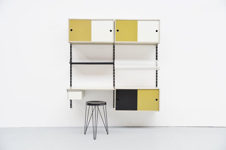 Very cool and complete shelving system / bookcase, designed by Tjerk Rijenga and manufactured by Pilastro, Holland 1960. This is a very nice medium sized and very complete wall unit with some nice options included. This unit contains some shelves, a
