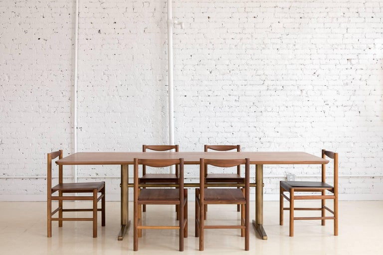 This contemporary dining table features a hardwood walnut top with rounded corners and a continuous bottom bevel that compliments details found on the brass pedestal base.   All base components are precision machined from steel and plated in brass