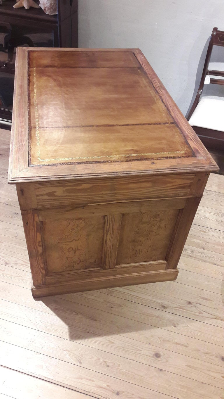 Small stripped pine desk with tan leather and great brass handles.