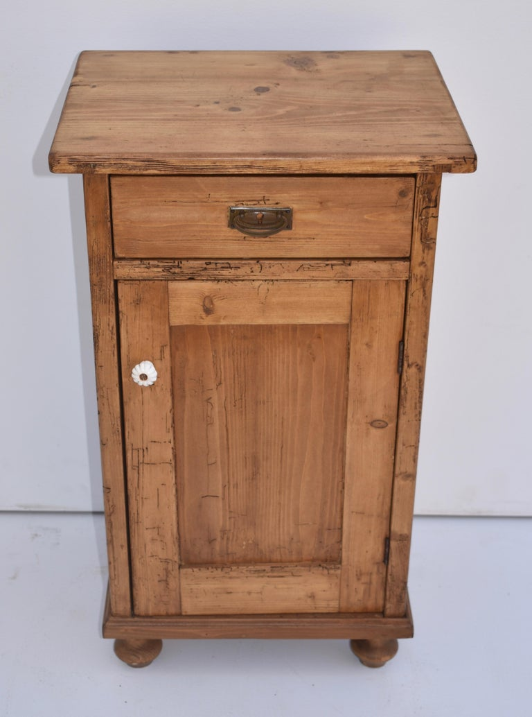 This single nightstand has one hand-cut dovetailed drawer and one paneled door, with a single shelf inside. It has significant attractive inactive woodworm tracks.