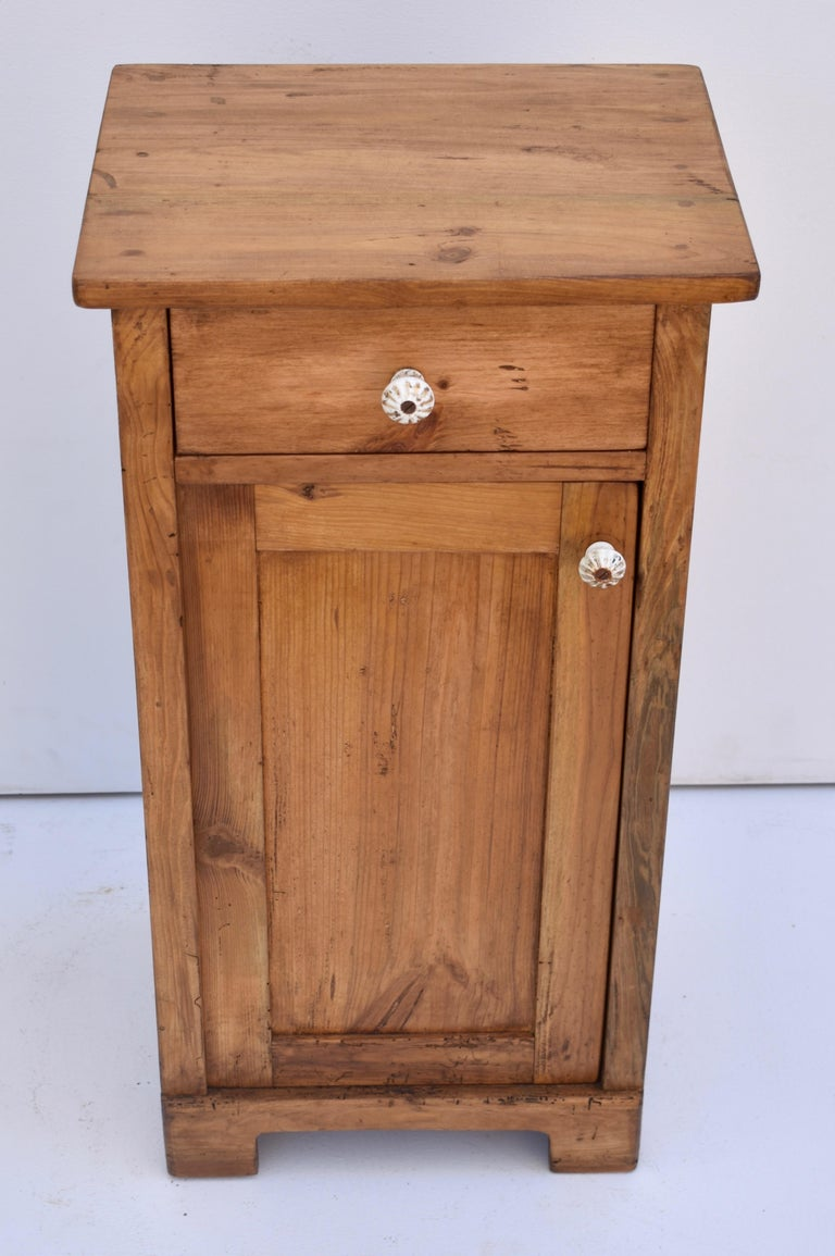 This is a plain and simple pine nightstand with one handcut dovetailed drawer and one paneled door with a single shelf inside.