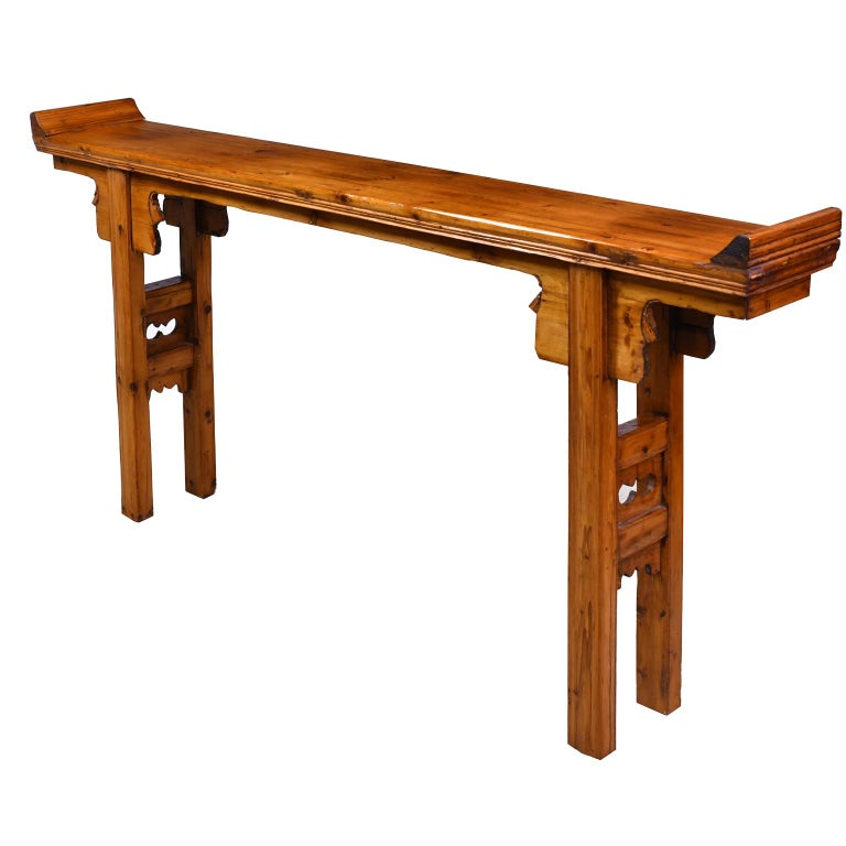 A Qing Chinese Altar table in elm and pine with everted ends on the top, square legs with carved stretchers and carved flanges. Shanxi, China, 20th century