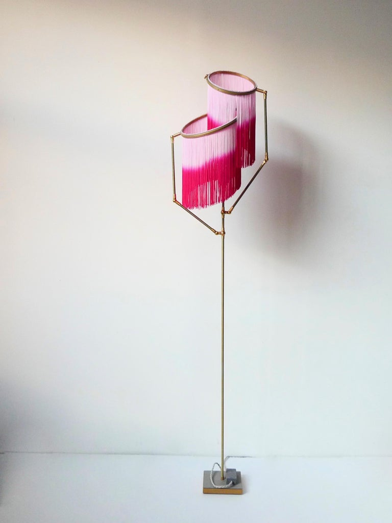 Pink charme floor Lamp, Sander Bottinga  Dimensions: H 153 x W 38 x D 25 cm Hand-sculpted in brass, leather, wood and dip dyed colored Fringes in viscose. The movable arms makes it possible to move the circles with fringes in differed