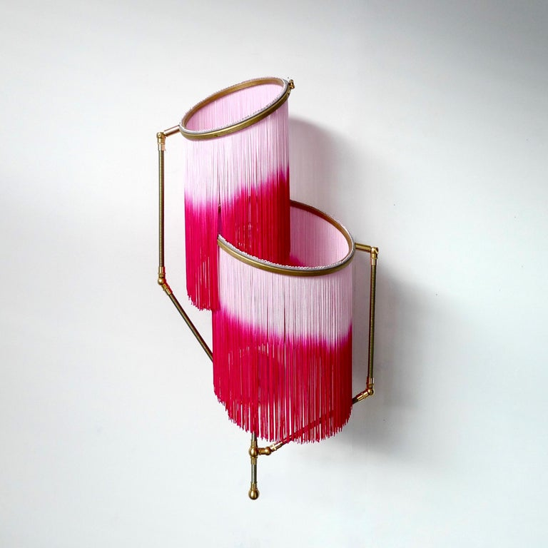 Pink charmed sconce lamp, Sander Bottinga  Dimensions: 50 x W 38 x D 27 cm Hand-Sculpted in brass, leather, wood and dip dyed colored Fringes in viscose. The movable arms makes it possible to move the circles with fringes in differed positions. So