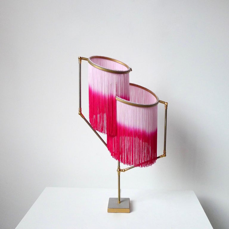 Pink charme table lamp, Sander Bottinga  Dimensions: H 73 x W 38 x D 25 cm Hand-sculpted in brass, leather, wood and dip dyed colored Fringes in viscose. The movable arms makes it possible to move the circles with fringes in differed positions. So