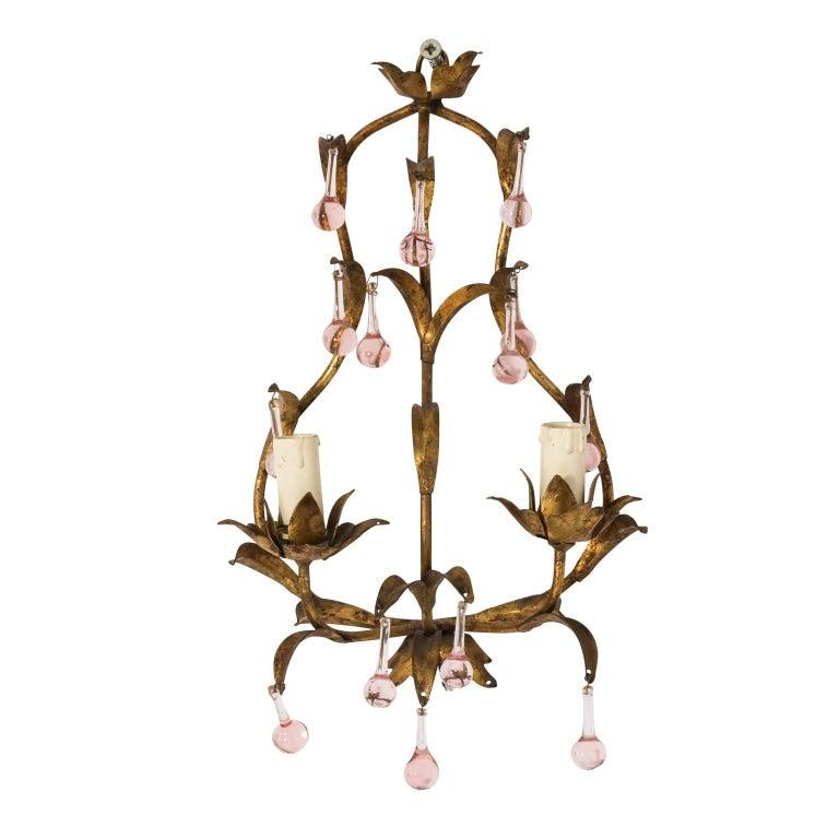 Elegant pair of gilded wall sconces with pink crystal drops, from France circa early 20th century. Gleaming gilded foliage frame is decorated with pink-hued teardrop crystals. These light fixtures have been rewired for modern use, ready for