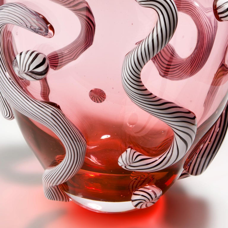 Pink hand blown glass object with black and white striped curls attached. Hand blown in Amsterdam.