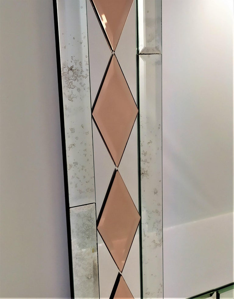 Rectangular Murano glass mirror, from the twenty-first century, composed of beveled and antiqued bands by hand, with the insert of pink crystal rhombuses faceted like diamonds all handmade, produced in a limited edition, to furnish luxurious homes