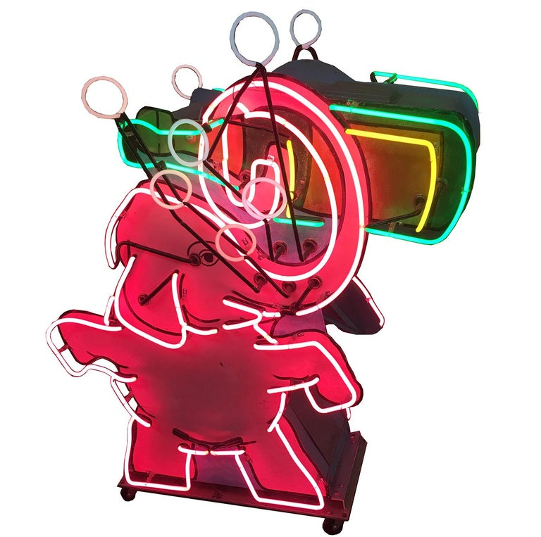 This whimsical pink elephant neon sign came from a 1950s liquor store in the Palm Springs area. He holds an animated bubbling bottle of champagne. The sign is double sided, with neon and the painted images on both sides. It is free standing, and we