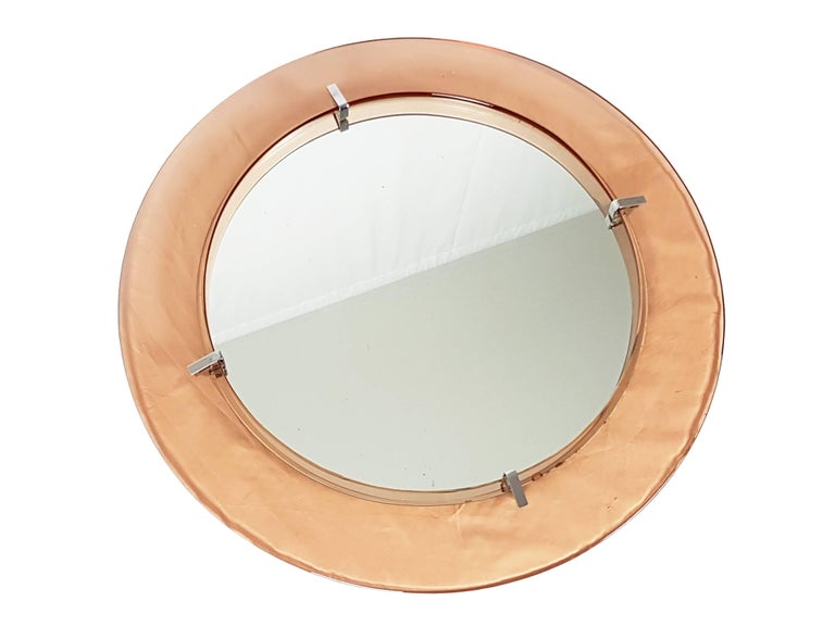 This round wall mirror was produced in Italy, circa 1960s. It made from a wooden and metal structure with a transparent pink frame joint together by four chrome-plated metal supports. It remains in very good condition: few oxidation spot on the