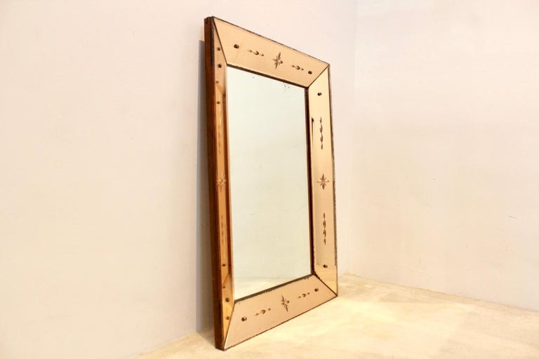 Impressive Venetian mirror with sophisticated etched patterns and constructed on a very solid Wooden back base. The mirror glass has a tremendous beautiful soft pink glow which combines perfectly with any background. Designed and made in the 1940s