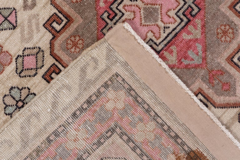 Khotan is the most active of the three Chinese Turkestan rug producing towns and this cream ground, three barbed and hooked medallion scatter is a good example of Interwar production. There is a star, lazy S, diamond and dot cluster background