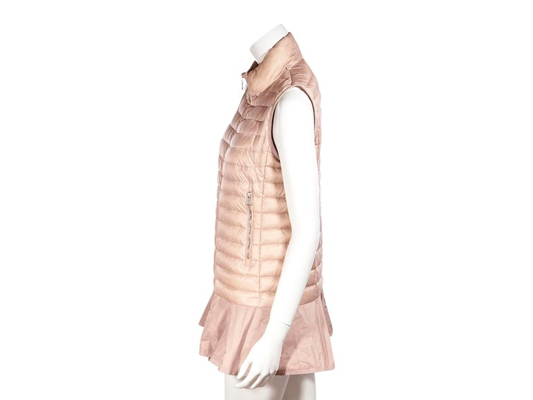 Product details:  Pink puffer down vest by Moncler. High collar. Goose down filled. Zip side pockets. Ruffled hem. Zip front closure. Gold-tone hardware. Pair yours with a cashmere long sleeve sweater. 36