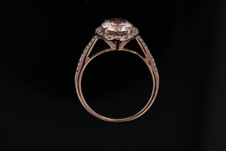 This pink morganite and diamond ring is crafted in 14kt rose gold, & contains an Oval Morganite (1.81 total carat weight) surrounded by 26 round diamonds (0.25 total carat weight, G color, SI clarity).