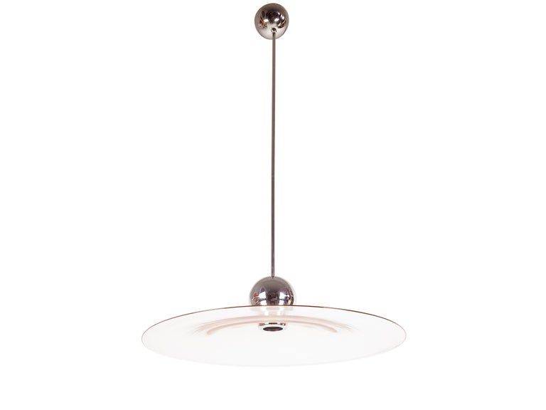 This elegant and light pendant was produced in Italy, circa 1970. It is made from a thin chrome-plated brass structure and a handmade pink Murano glass round conic shade. The rod, which is made up of 2 parts, is quite long and can be shortened by