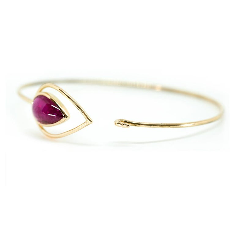 Oval 18K yellow gold rigid bracelet, set with a luminous pink tourmaline cabochon pear. Easy to put on and take off Tourmaline weight: 5.96 carats Total weight: 8.62 grams French assay Mark Created by Marion jeantet  Price without local taxes.