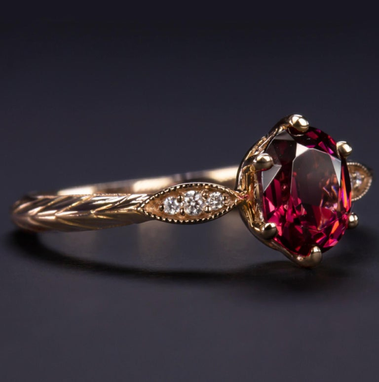 Exquisite rhodolite garnet and diamond ring is positively gleaming with eye catching sparkle and rich color! The oval cut rhodolite garnet center has a vibrant and highly saturated fuschia hue that stands out strikingly against the bright white