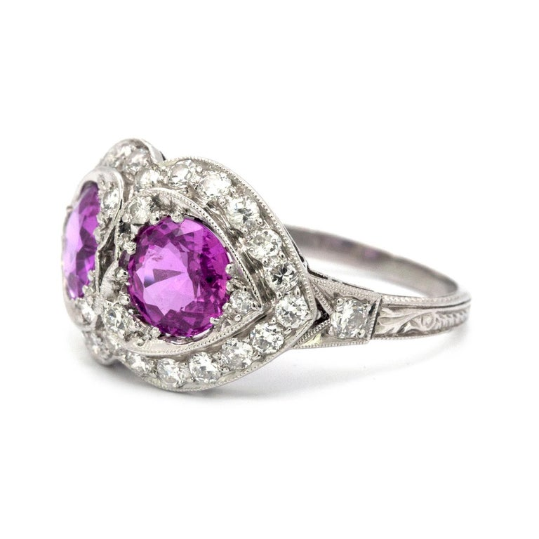 This Pink Sapphire and Diamond, Art Deco style, 18k white gold ring features two round Pink Sapphires. Each one measures 6.5 mm and have a total weight of 2.45 cts. These pink sapphires are beautifully offset by 32 rbc clean white diamonds that