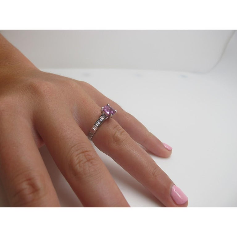 A vibrant bubblegum-pink sapphire is featured in this ring. It is brilliant and bright and cushion-cut, measuring 7.2x7.2mm and weighing 1.78 carats. The sapphire is flanked by baguette-cut diamonds that weigh a total of .26 carats. Beautiful for