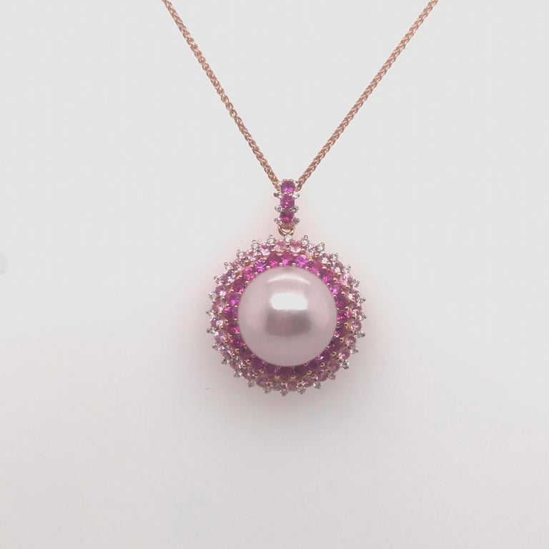 18K Rose Gold pendant necklace featuring one Pink Freshwater pearl measuring 13-14 mm flanked with pink sapphires weighing 1.97 carats and 36 round brilliants weighing 0.22 carats.