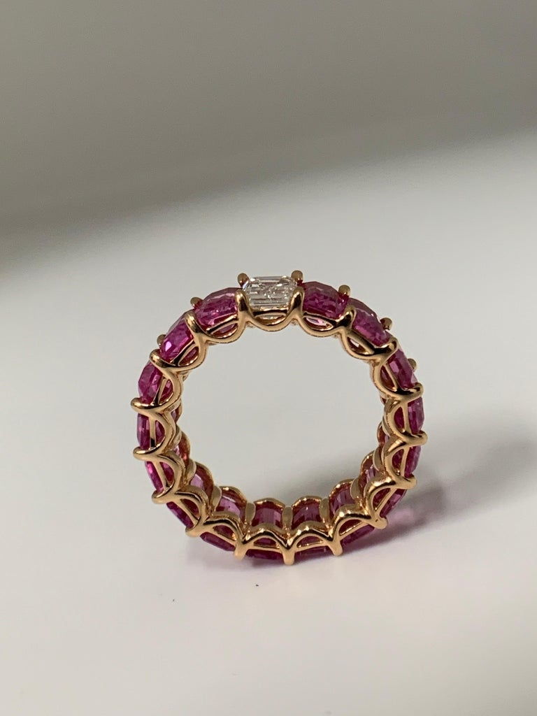 Beautiful and Forward Eternity Band. Ring features 16 perfectly matched Pink Sapphires weighing 11.14 Carats and 1 Emerald Cut Diamond weighing 0.71 Carats. Set in 18 Karat Rose Gold. Size 6. Can be worn Diamond Side up or down.