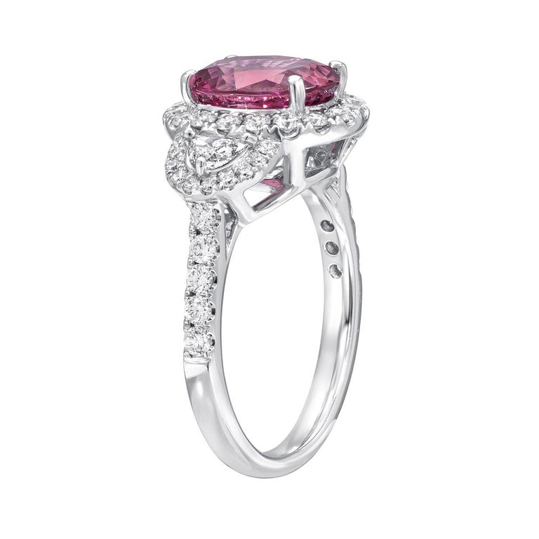 Pink Sapphire ring featuring a vibrant 3.14 carat oval Pink Sapphire, in a 18K white gold cocktail ring or engagement ring, adorned by a total of 0.89 carats of diamonds. Size 6. Resizing is complementary upon request. ***Returns are accepted and