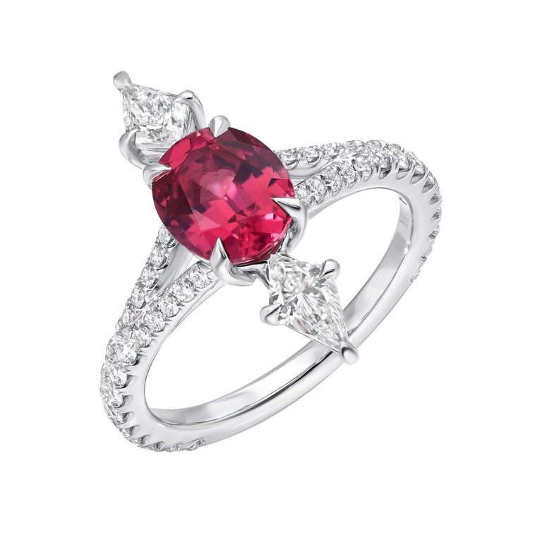 Hot Pink Spinel oval, weighing a total of 1.47 carats, is joined by a pair of kite shaped diamonds, E/VS1, weighing a total of 0.48 carats, and adorned by a total of 0.50 carats of round brilliant diamonds on the shank, to create this magnificent