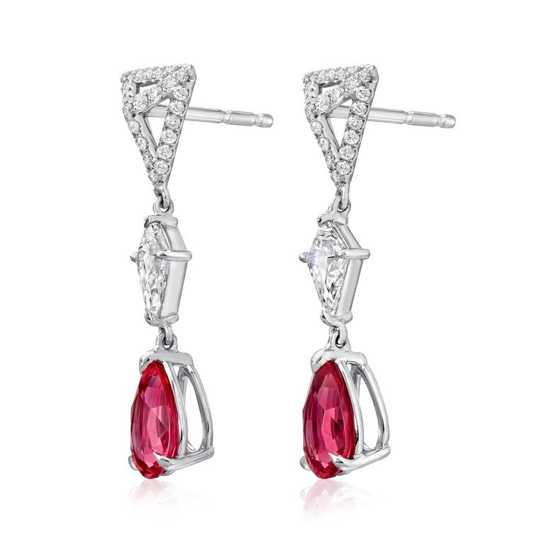 Hot Pink Spinel pear shapes, weighing a total of 1.83 carats, suspending from our signature three dimensional, eight millimeter triangle studs, set with a total of 0.30 round brilliant diamonds, and a pair of kite shaped diamonds weighing a total of