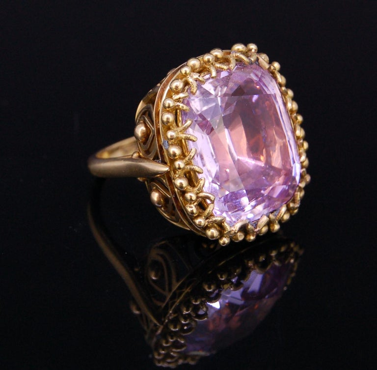 PINK TOPAZ 18-ct GOLD RING, set with a cushion cut pink topaz of 20.30 ct. in an openwork cullet, decorated with granulation. Size L. 13.8 grams. Accompanied by GCS London report No. 80241-00, stating that the approx. 20 ct. Pink topaz is natural.