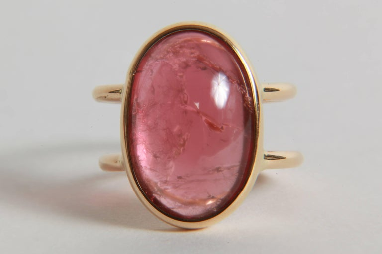 A pastel pink colour for this beautiful and voluminous ovale cabochon on a double 18K yellow gold ring. Simple and elegant.  Tourmaline cabochon : 17.12 carats  finger size : 52.5 or 6 1/4.  Can be sized. French assay mark, created by Marion