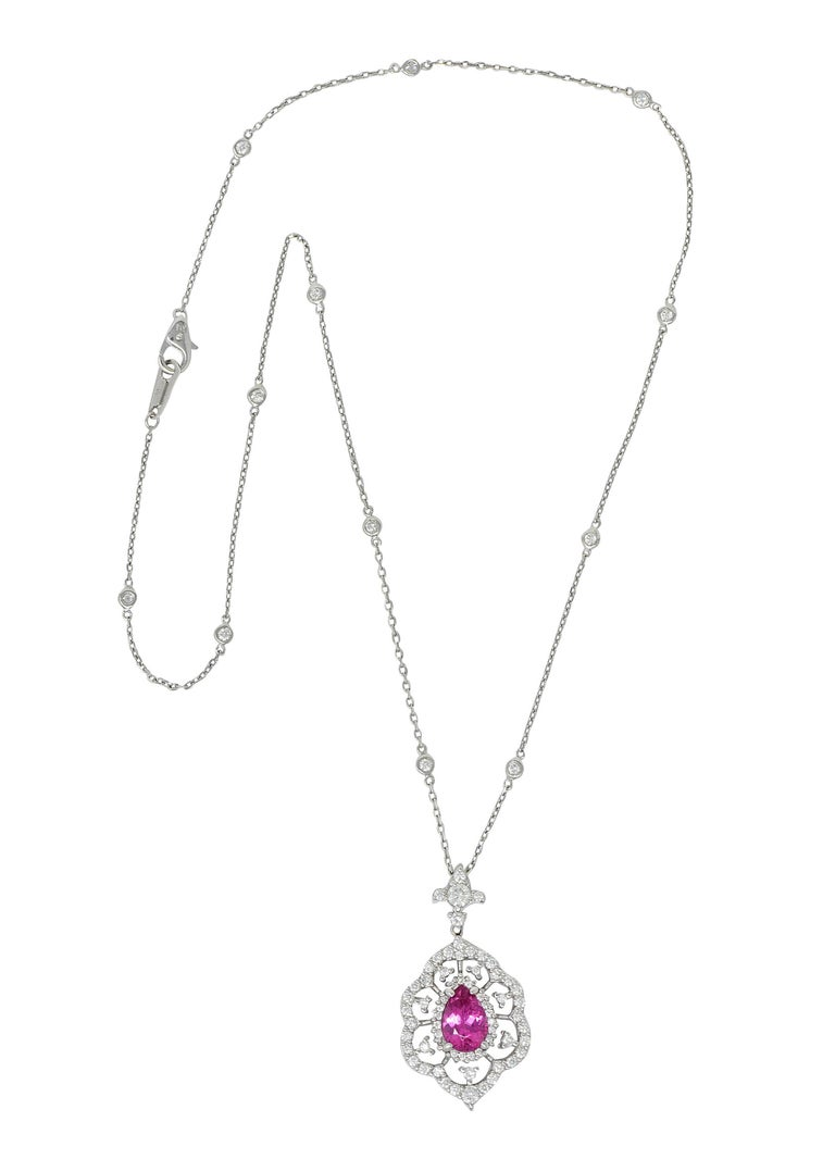 Diamonds-by-the-yard style cable chain necklace features ten bezel set round brilliant cut diamond stations  Suspending a grandiose cluster pendant centering a pear cut tourmaline measuring approximately 10.0 x 6.2; hot pink in color  With a