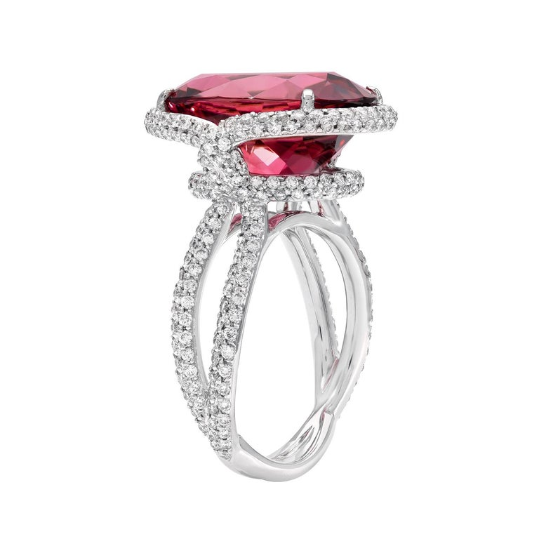 White gold diamond ring showcasing a spectacular 11.69 carat oval Rubellite Tourmaline, accented by a total of 1.16 carat round brilliant diamonds.  Crafted in 18K white gold. Size 6. Resizing is complementary upon request.  Returns are accepted and