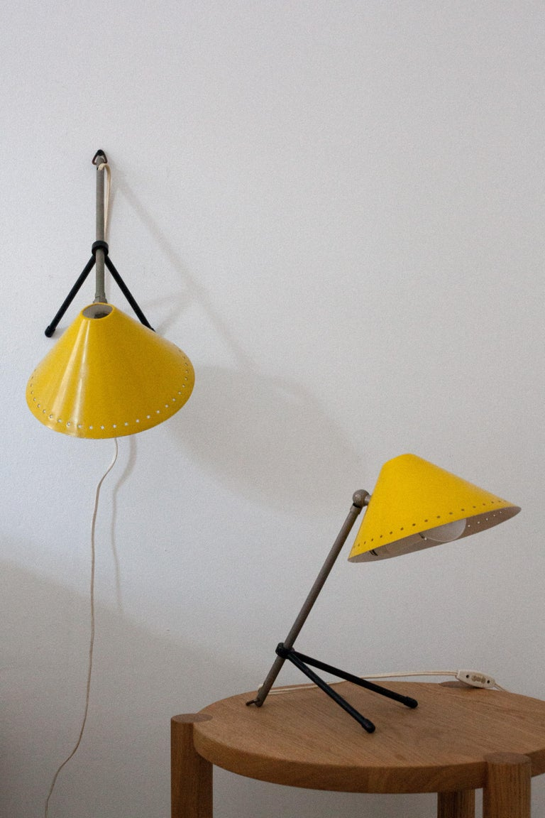 Bright yellow enamel Pinocchio lamp pair. Can be oriented as a table lamp or hung as a wall sconce. The lamps adjust in many directions. 