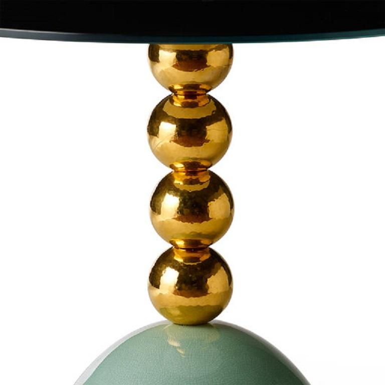 The brass structure of this side table supports a glass round top with a colored back. Four spheres adorn the vertical support crafted of enameled ceramic. The color of the base is turquoise with a crackled finish.