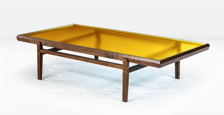 The Pintor coffee table's solid wood frame with brass inlay is engineered with chamfered edges to provide a simple but worthy setting for the jewel toned, colored glass which forms the tabletop. Shown with solid American black walnut frame and