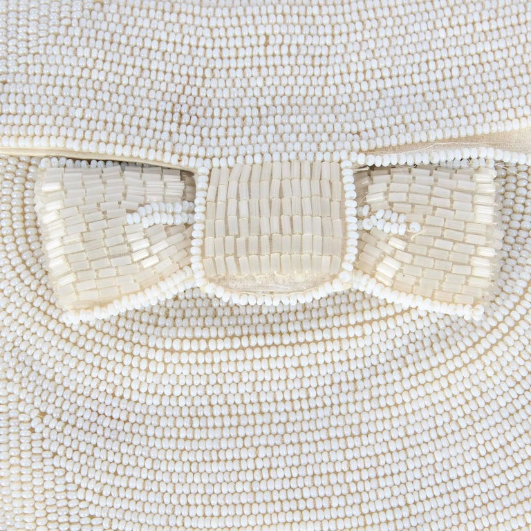 Pretty Pirovano flat beaded pochette, with white beads decoration all over, and a small bow. It includes a small mirror. Pression button closure. The item is vintage and was produced in the 50s : it shows some loosen threads (see the pictures) and
