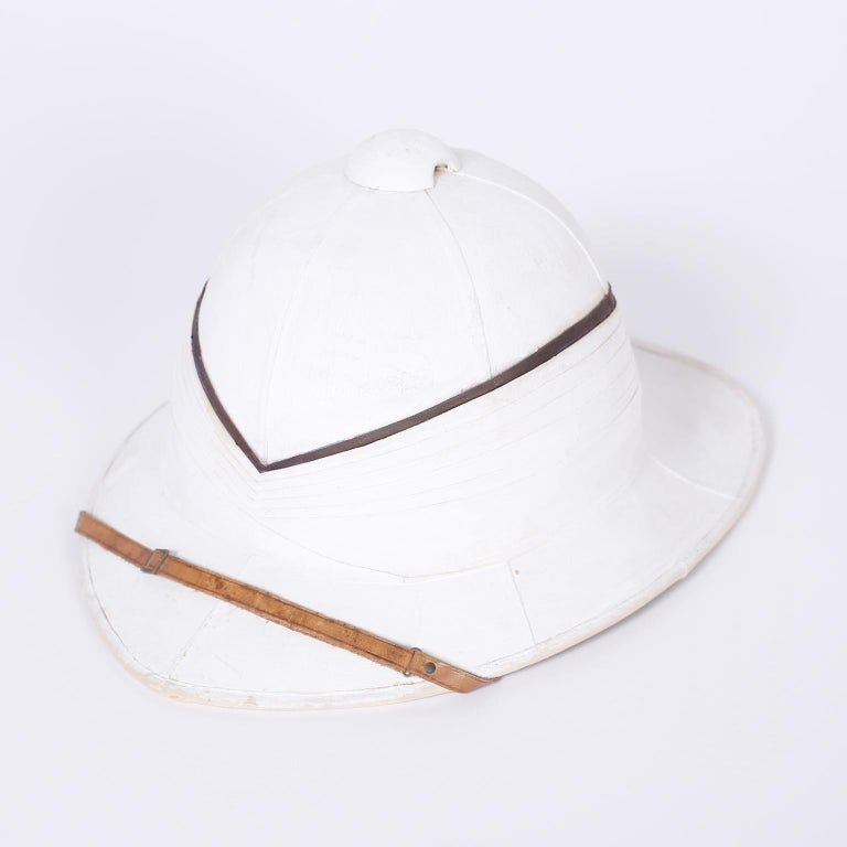 English pith helmet and painted copper box with all the historical romance you could wish for. Originally purchased from Gieves and Hawkes London by F.C.L. Halliday, a decorated Royal Navy officer in WWI.  Metal case measures: H 14, W 16, D