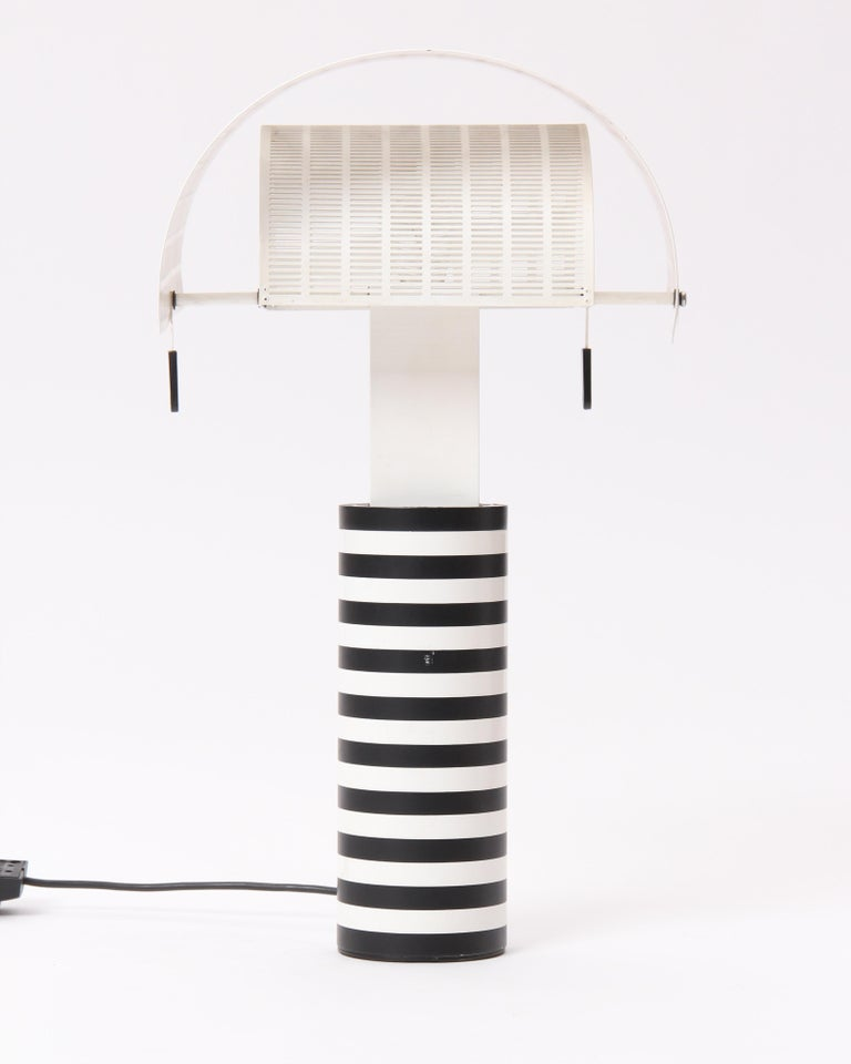 A 'Shogun' table lamp designed by Mario Botta with pivoting, slit-perforated white steel shades on a black and white striped cylinder base. Made by Artemide in Italy, circa 1986.