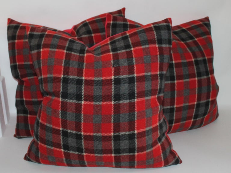We have two different styles and colors of holiday plaids. There are burnt orange and black wool plaid Pendleton pillows. There are two pairs of these in stock. All in pristine condition with black cotton linen backings. The next colors are black