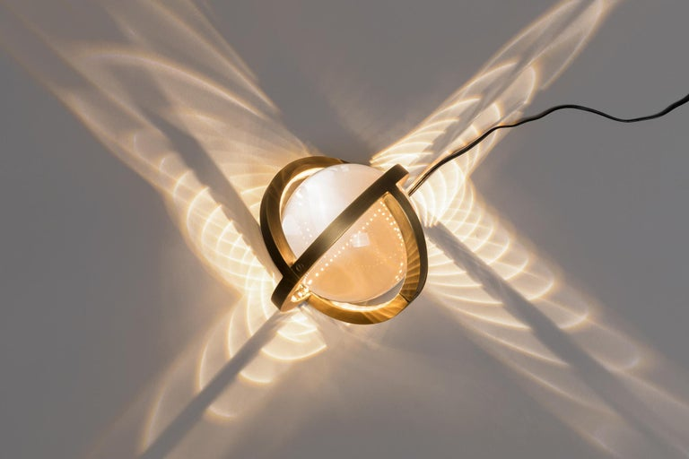 The new Planetaria lights are both geometric and organic. The lights rep-resent an exploration of the globe; one created by folding and rotating three flat circles to create a single sphere, which itself encases a reflective glass orb. The seed pod