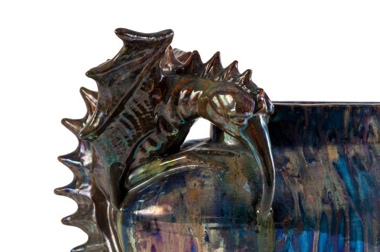 This stoneware planter with its iridescent decoration surprises by its dimensions as well as by its original iconography. Its oval neck widens slightly along its entire length, while its rounded ends display a remarkable sculpted decoration in the
