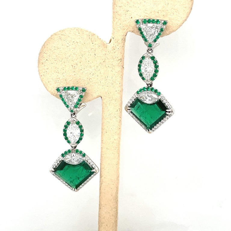 Absolutely breathtaking art deco inspired emerald and diamond earrings. Designed with 2 gem quality heart shaped emeralds weighing 6.74 carats. There are 2 trillion diamonds of F color VS clarity weighing 1.47 carats, and 4 marquise diamonds F color
