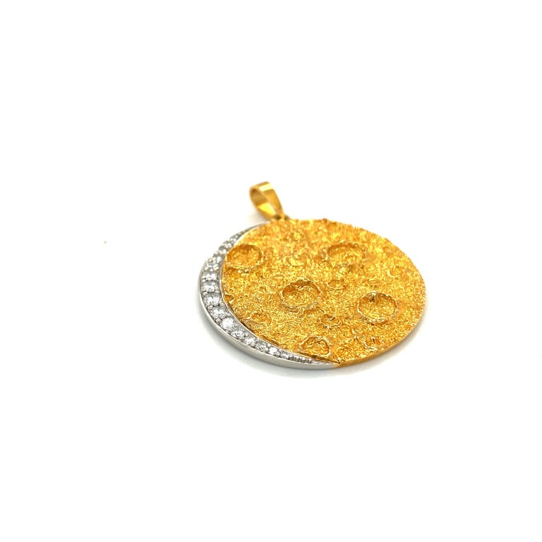 Thia 18 karat yellow gold pendant is crafted in a sand blasted finish. The pendant is designed with a texture to give the feel of the moon's craters. A platinum crescent set with 0.45 carats of round brilliant diamonds borders the pendant. Stamped