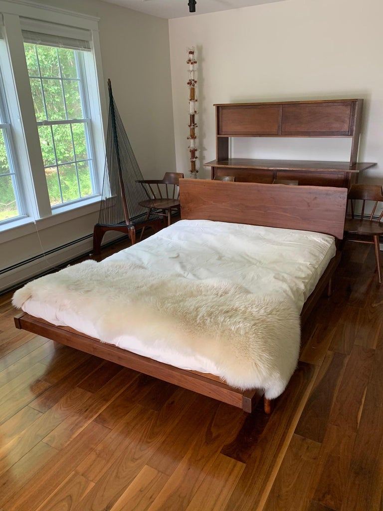 Platform bed studio crafted by George Nakashima circa 1960s. It features a mounted walnut slab headboard that display free edge on top. The slab itself is 16.5 inches in height. The bed is supported by four feet with typical wood joints.  The
