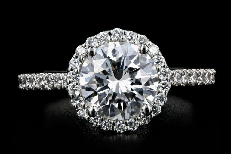 Era: New  Composition: Platinum  Primary Stone: Round Brilliant Cut Diamond   Carat Weight: 1.56 Carats  Color: F  Clarity: SI1  Accent Stone: Round Brilliant Cut Diamonds  Carat Weight: .42 Carats  Color: G-H  Clarity: VS1/2  Total Carat Weight: