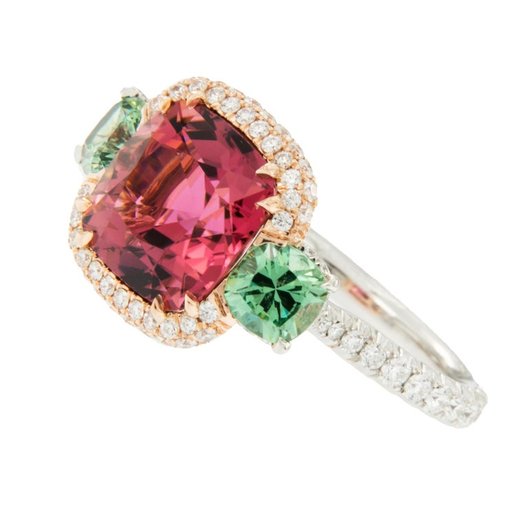 Made in New York & known for his superb, finest quality gems & craftsmanship, this exceptional ring showcases a lovely hued Rubelite set in 18 karat rose gold diamond halo, flanked by 2 natural, unenhanced Demantoid Garnets = 1.28 Cttw. Demantoid's