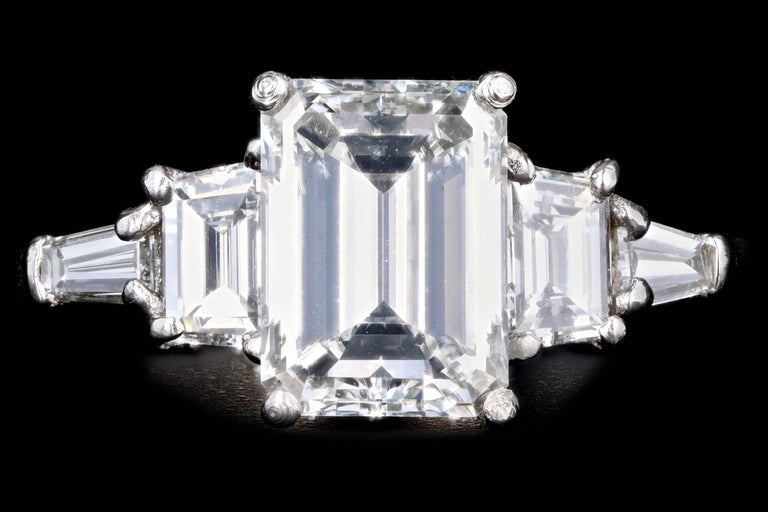Era: Modern  Composition: Platinum   Primary Stone: Emerald Cut Diamond  Carat Weight: 2.03 Carats  Color/Clarity: H / VS2  Accent Stone: Trapezoid & Tapered Baguette Cut Diamonds  Carat Weight: .75 Carats Total  Color/Clarity: G-H / VS1-2  Total