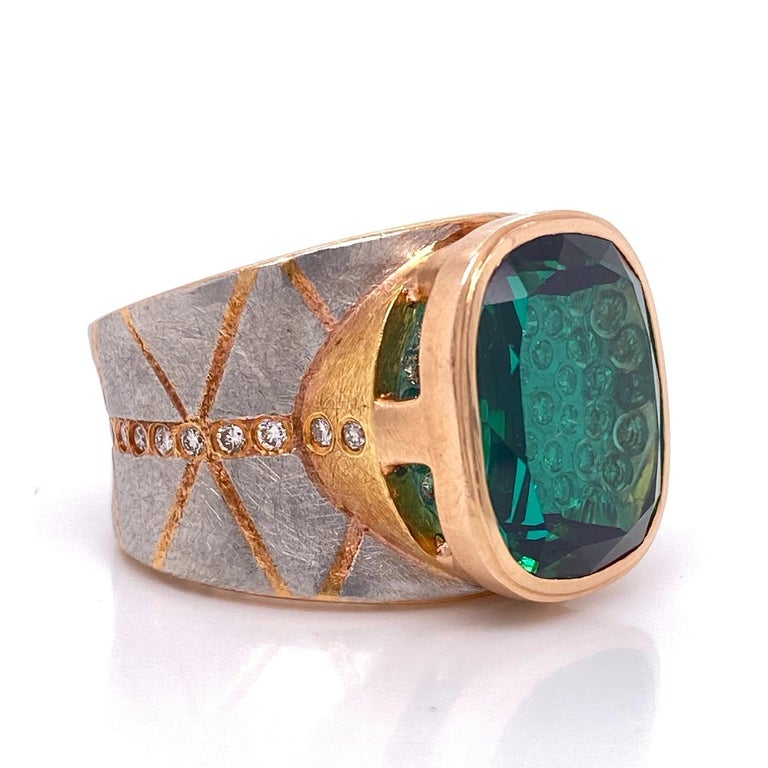A platinum and 18k rose gold ring set with a 16.12mm x 13.08mm lens cut green tourmaline and 60 round full cut diamonds for a .9 total carat weight.  Designed and made by llyn strong and Michael Zobel as a collaboration.