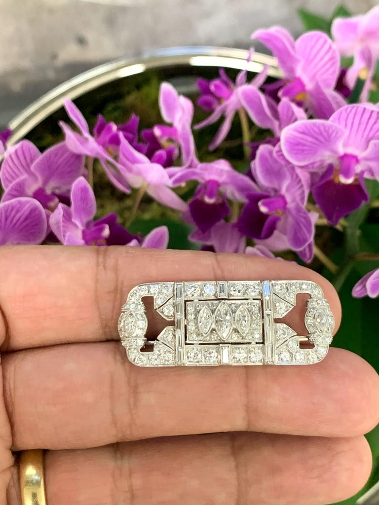 A Platinum and Diamond Art Deco Pin,  Circa 1930's  This Art Deco pin contains 89 natural diamonds , including 1 Marquise (7.5 mm x 3.5mm), 4 Marquise ( 4mm x 2mm ) 12 Straight Baguettes ( 1.7mm x 4mm ) and 48 Round and single cut diamonds measuring